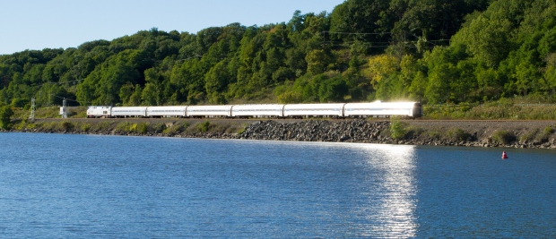Passenger train along river with sun reflection